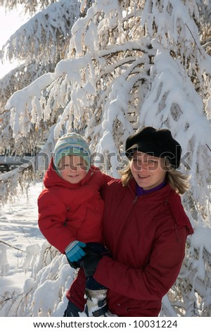 Happy family (mother with small boy) in winter snow covered city park - stock photo