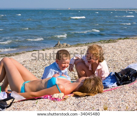 happy family (mother with small children) relax on beach