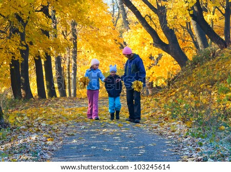 Happy family (mother with small children) walking in golden maple autumn park
