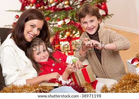Happy family: mother with son and daughter on Christmas