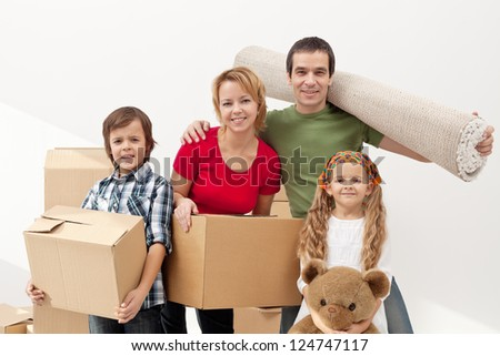 Happy family moving into a new home carrying their stuff