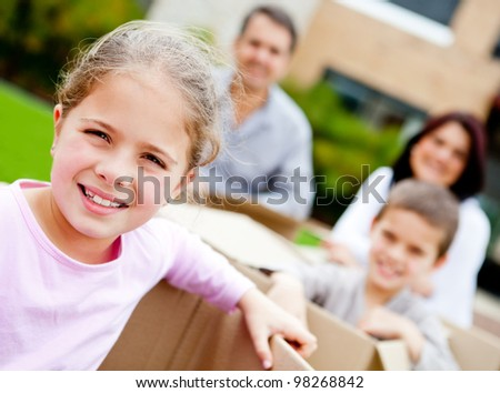 Happy family moving to a new house and carrying boxes - stock photo