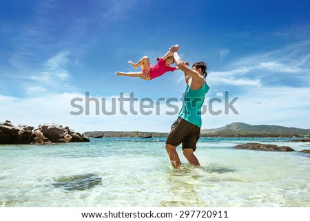 Happy family of father and daughter having fun on the beach