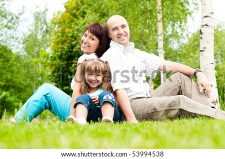 happy family of father and mother and their daughter on grass in park. All smiling and looking in camera (focus on daughter)
