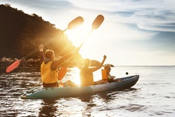 Happy family of father mother and son kayaking and having fun at sunset sea bay