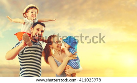 happy family of father, mother and two children, baby son and daughter on  the beach at sunset #411025978