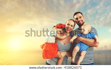 happy family of father, mother and two children, baby son and daughter on  the beach at sunset #418826071