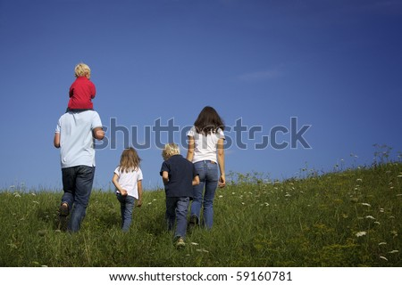Happy family of five walking together in field, view from back.