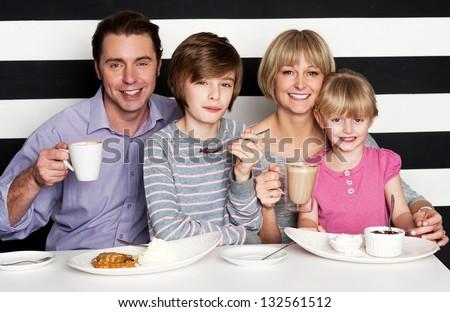 Happy family of four enjoying breakfast at a restaurant.