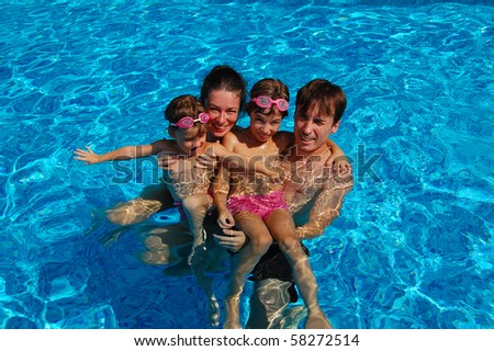 Happy family of four having fun in the swimming pool