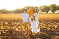 Happy family of four in a field, all dressed in white.
