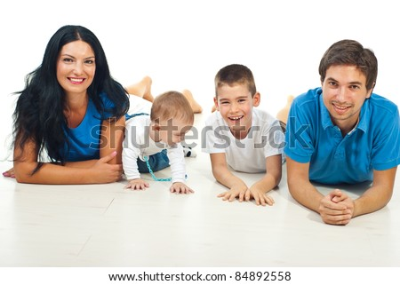 Happy family of four members lying on floor together and smiling against white background