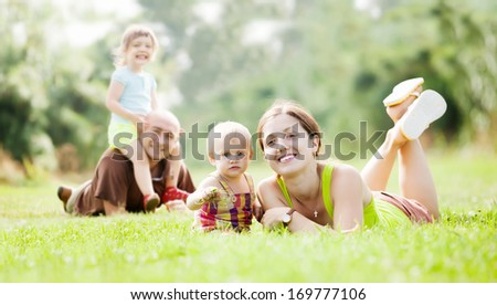 Happy family of four on grass in summer park