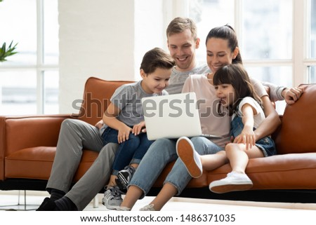Happy family of four parents and cute little kids children enjoy using laptop watching cartoons, make internet video call or shopping online looking at computer screen sit together on sofa at home