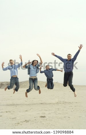 happy family of four people jumping outdoors