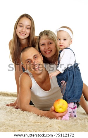 happy family of four people lying on the carpet on background