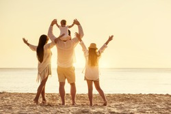 Happy family of four peoples are standing with raised arms at sunset sea beach