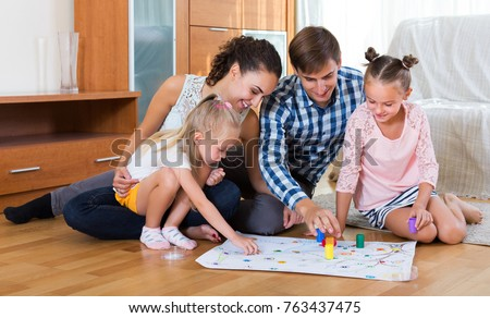 Happy family of four playing at board game in domestic interior