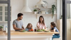 Happy family of four preparing healthy food salad together at kitchen. Smiling young parents chopping vegetables while little preschool children waiting for food, communicating, enjoying weekend time.