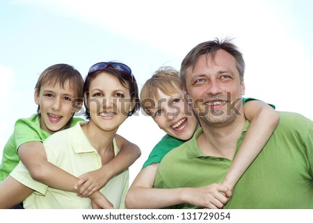 happy family of four spends time outdoors in the summer