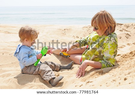 happy family of kid and mother playing with the sand on the beach