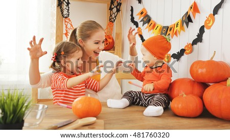 Happy family of mother and children prepare for Halloween pumpkins decorate the home
