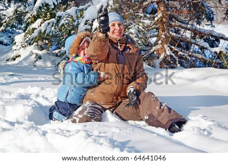 happy family of mother with kid playing in the snow winter park