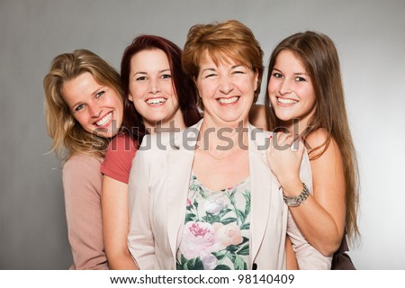 Happy family of mother with three daughters isolated on grey background. Fashion style studio portrait.