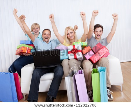 Happy family of online shoppers laden with gifts sitting around the father who is sitting with his laptop computer on his lap - stock photo
