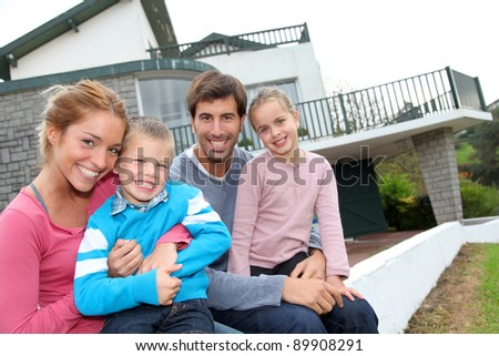 Happy family of 4 people sitting in front of new home