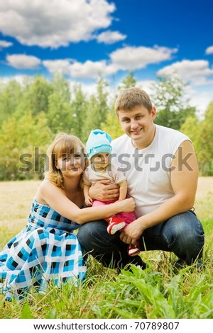 Happy family of 3 people sitting on grass under summer sun - stock photo