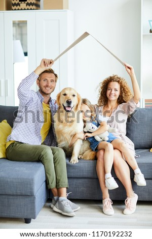 Happy family of three and their fluffy pet sitting on sofa with imaginry roof over their heads