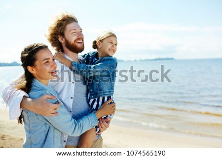 Happy family of three embracing while enjoying hot summer day on the beach at leisure