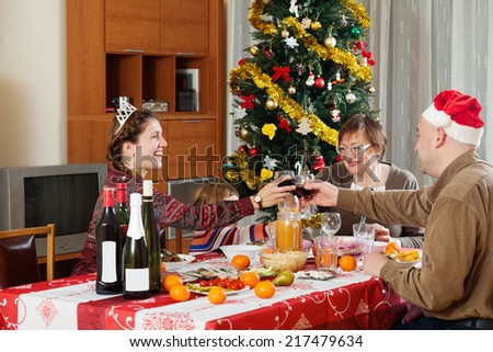 Happy family of three generations celebrating New Year over celebratory table at home   #217479634