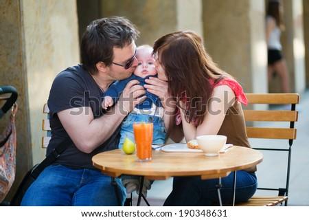 Happy family of three having breakfast in a cafe #190348631