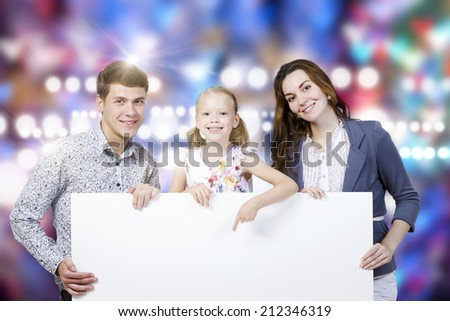 Happy family of three holding white blank banner. Place for text