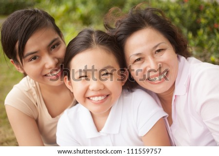 Happy family of three looking at camera outdoors