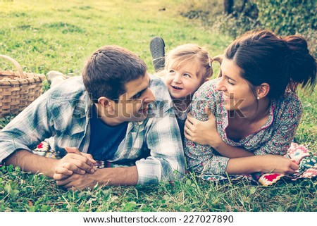 happy family of three lying in...