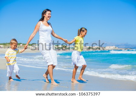 Happy family of three - mother and her child running and having fun on tropical beach