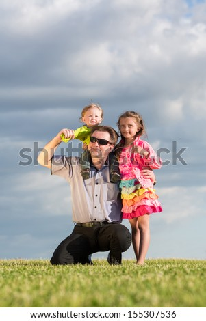 Happy family of three on green grass and blue sky, father sat down and put  son on the neck.
