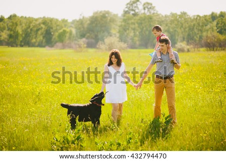 Happy family of three people hugging outside. Mother in expectation of baby. Smiling faces of woman, man and child. Baby playing with parents. Togetherness. Happy family in sunset time in countryside.