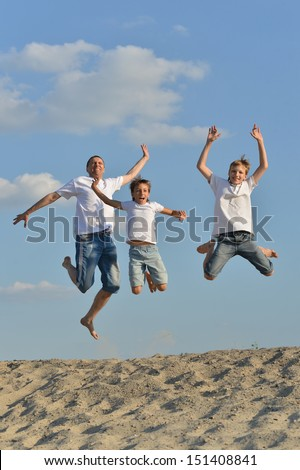 Happy family of three people jumping outdoors