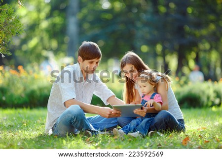 Happy family of three people relaxing in a city park. Father shows in tablet funny pictures. Family sitting on grass and looking at the tablet. Happy family concept of the good life.