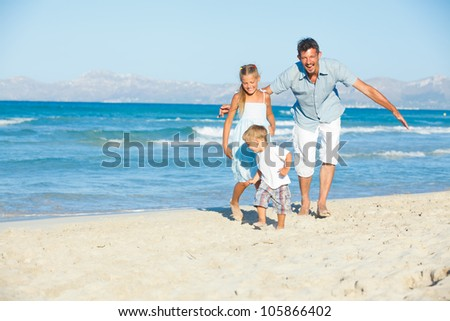 Happy family of three running and having fun on tropical beach