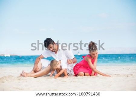 Happy family of three sitting and having fun on tropical beach