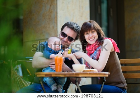 Happy family of three spending their time together in an outdoor cafe