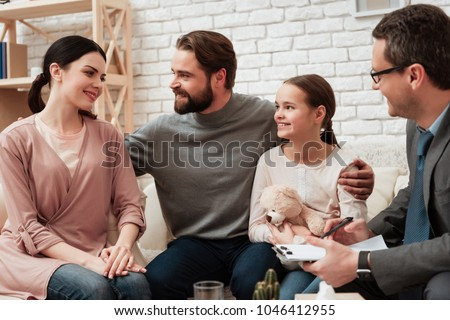Happy family of three talking with psychologist. Family psychotherapy concept. Visit to family psychologist. Psychological help for family.
