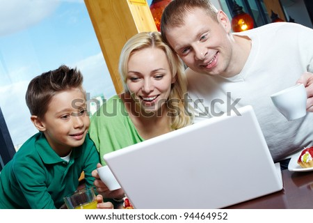 Happy family of three using a laptop while having lunch