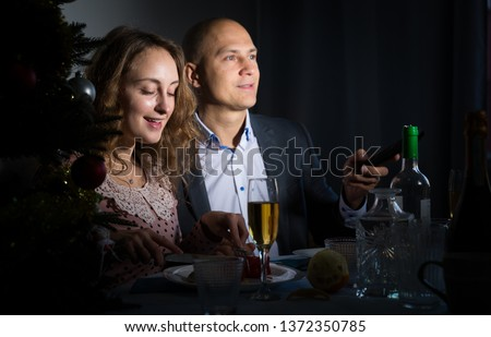 Happy family of two celebrating New Year, enjoying dinner at home at night and watching tv