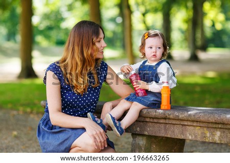 Happy family of two:  young mother and adorable baby daughter playing together in summer park and having fun together, outdoors.